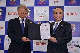 「サッカー日本代表オフィシャルパートナー」の契約更新を発表するサッカー協会の大仁会長(左)とキリンの磯崎社長