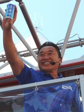 「本田応援缶」を掲げる松木安太郎さん