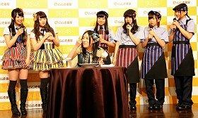 キーマカレーをほおばって笑顔を見せるSKE48の松井珠理奈さん(中央)。後列は左から高柳明音さん、木本花音さん、柴田阿弥さん、古川愛李さん、大場美奈さん、古畑奈和さん。右側4人が新制服を着ている