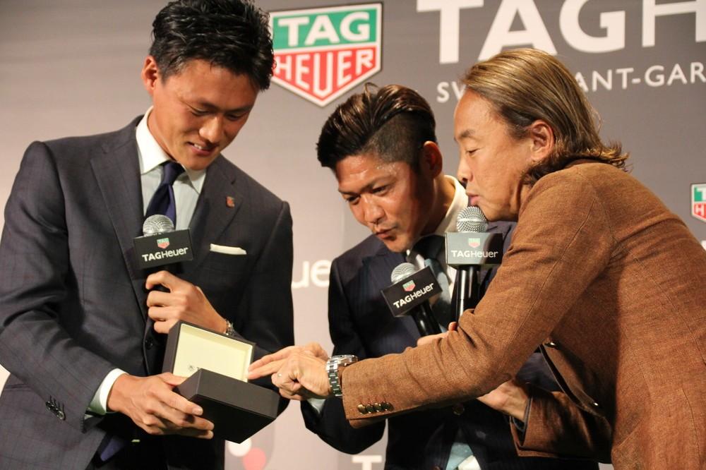 タグ・ホイヤーの最新モデルの腕時計を持つ李忠成(左)と、興味深く見つめる大久保嘉人(中)、北澤豪