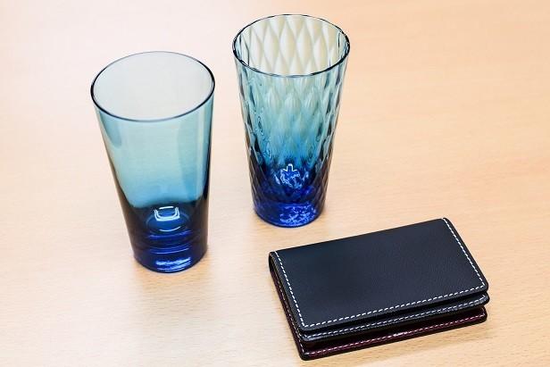 ブルーの綺麗なガラスのコップは、廃車のガラスから再生した。手前の黒の財布は、廃車の革シートから再生した。静脈産業から生み出された製品だ