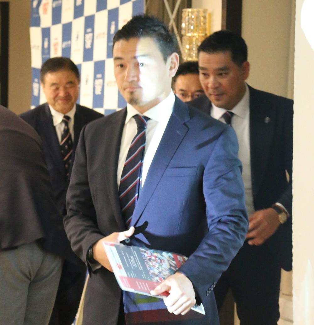 多くのフラッシュを浴びながら、壇上を後にする五郎丸歩選手。右は元日本代表の増保輝則氏。左奥は衆議院議員の遠藤利明氏