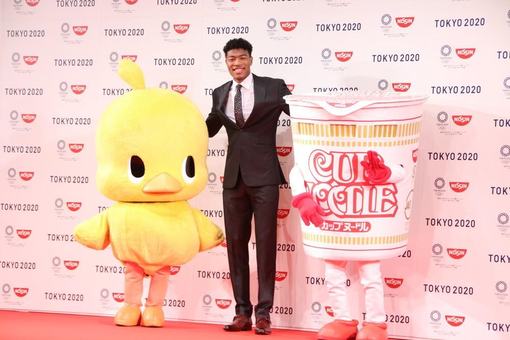 日清食品のキャラクター「ひよこちゃん」(左)、「カップヌードル君」(右)と肩を組む八村選手