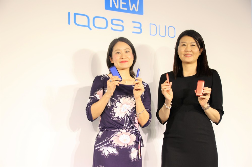 「IQOS 3 DUO」を持つシェリー・ゴー社長(右)と坂牧真美氏
