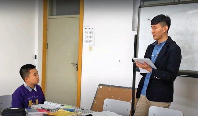 大学の講師からマンツーマンで英語の授業を受ける小学生