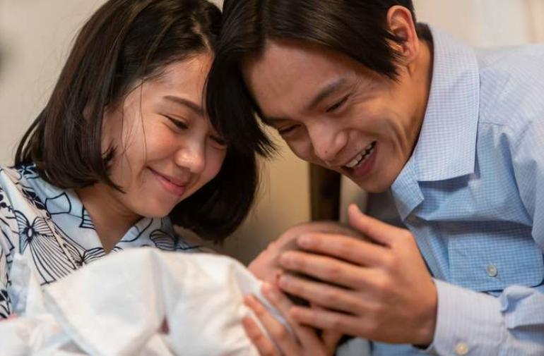 赤ちゃんを抱く音と裕一(NHK「エール」の番組ホームページより)
